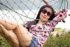 Härlig kvinna på hängmattan fotografering för bildbyråer