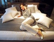 Härlig kvinna på säng Arkivfoton