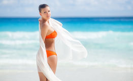 Härlig kvinna på stranden i orange bikini Royaltyfri Foto