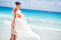 Härlig kvinna på stranden i orange bikini Royaltyfri Bild