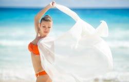 Härlig kvinna på stranden i orange bikini Arkivbilder
