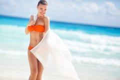 Härlig kvinna på stranden i orange bikini Fotografering för Bildbyråer