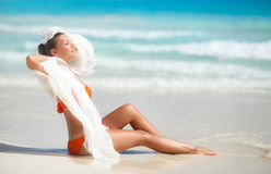 Härlig kvinna på stranden i orange bikini Arkivfoton