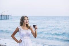 Härlig kvinna på stranden med ett exponeringsglas av vin i den vita klänningen Arkivbild