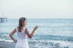 Härlig kvinna på stranden med ett exponeringsglas av vin i den vita klänningen Royaltyfri Fotografi
