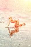 Härlig kvinna på stranden vid havet arkivfoto