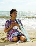 Härlig kvinna på strandläsningbokstaven Royaltyfri Foto