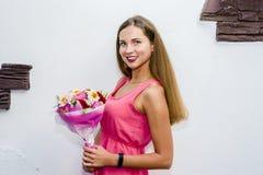 Härlig kvinna på vit bakgrund i rosa klänning ung flickainnehavbukett av blommor arkivfoton