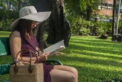 Härlig kvinna, purpurfärgad klänning som sitter på en bänk och läser i trädgården royaltyfri foto