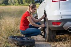 Härlig kvinna som ändrar det plana gummihjulet i fält Royaltyfria Bilder