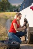 Härlig kvinna som ändrar det plana gummihjulet på den lantliga vägen Royaltyfri Bild