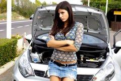 Härlig kvinna som är SAD med den broken bilen royaltyfria foton