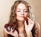 Härlig kvinna som äter en chokladkonfekt arkivfoton