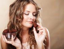 Härlig kvinna som äter en chokladkonfekt royaltyfria foton
