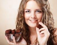 Härlig kvinna som äter en chokladkonfekt arkivbild