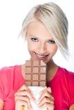 Härlig kvinna som äter en stor stång av choklad royaltyfri foto