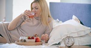 Härlig kvinna som äter frukosten med yoghurt, frukt och sädesslag på säng Morgonvak upp hemma in sovrum caucasian stock video