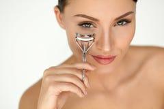 Härlig kvinna som använder ögonfranshårrullen på lockiga långa ögonfrans Arkivfoton
