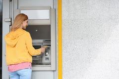Härlig kvinna som använder bankomaten Utrymme f?r text royaltyfri bild