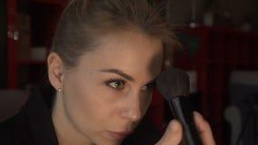 Härlig kvinna som använder den kosmetiska borsten för rodnad och pulver i sminkframsida stock video