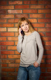 Härlig kvinna som använder den tekniskt avancerade smartphonen mot tegelstenväggen. Arkivfoto