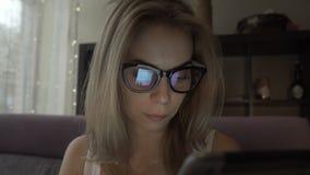 Härlig kvinna som använder modern minnestavlaPC, och skärm som reflekterar i exponeringsglas stock video