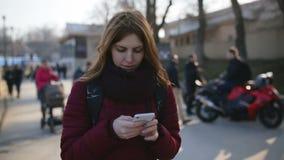 Härlig kvinna som använder smart telefonteknologi app i stadsgator på den kalla soliga dagen lager videofilmer
