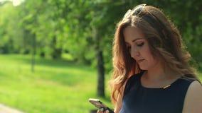 Härlig kvinna som använder smartphoneapp-teknologi i parkera stock video