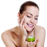 Härlig kvinna som applicerar fuktighetsbevarande hudkrämkräm Arkivbild