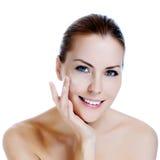 Härlig kvinna som applicerar fuktighetsbevarande hudkrämkräm Fotografering för Bildbyråer