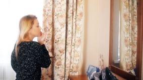 Härlig kvinna som applicerar makeup på spegeln för framdel för hudframsidaanseende i hem stock video