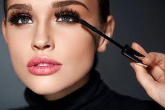 _ Härlig kvinna som applicerar svart mascara på ögonfrans Arkivbild