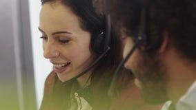 Härlig kvinna som arbetar i ett call centerkontor med mitt - östlig man stock video