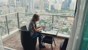 Härlig kvinna som arbetar på balkong arkivfilmer