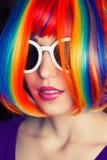 Härlig kvinna som bär den färgrika peruken och vita solglasögonagains Arkivfoto