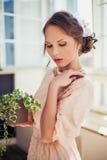 Härlig kvinna som bär den långa växten för klänninginnehavhus Royaltyfri Bild