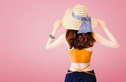 Härlig kvinna som bär en sugrörhatt och en sexig dräkt på rosa bakgrund med sommarbegrepp royaltyfria foton