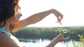 Härlig kvinna som balanserar två rastlös människaspinnare på tummar, ultrarapid stock video