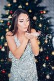 Härlig kvinna som blåser snö som isoleras på guling härlig slående snowkvinna royaltyfria bilder