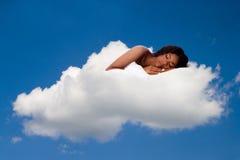 Härlig kvinna som djupt är sovande och drömmer på moln nio Arkivbild
