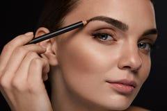 Härlig kvinna som drar upp konturerna av ögonbryn med blyertspennan _ Arkivfoton