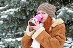 Härlig kvinna som dricker en varm drink och uppehälle som är varma på den utomhus- vintern, snöig granträd i skogen, långt rött h arkivbilder
