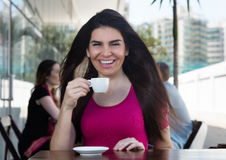 Härlig kvinna som dricker ett kaffe i en restaurang arkivbilder