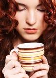 Härlig kvinna som dricker kaffe över beige backgound Fotografering för Bildbyråer