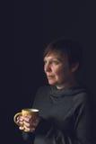 Härlig kvinna som dricker kaffe i mörkt rum Fotografering för Bildbyråer