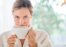 Härlig kvinna som dricker kaffe i vård- Spa