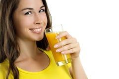 Härlig kvinna som dricker orange fruktsaft Arkivbilder