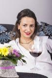 Härlig kvinna som dricker vinsammanträde på en soffa Fotografering för Bildbyråer