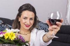 Härlig kvinna som dricker vinsammanträde på en soffa Royaltyfri Foto
