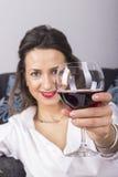 Härlig kvinna som dricker vinsammanträde på en soffa Arkivfoto